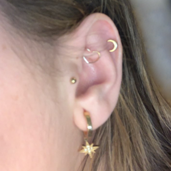 עיצוב אוזן של עגיל רוק חישוק לב עם עגיל הליקס צמוד, עגיל טראגוס צמוד ועגיל חישוק רגיל באוזן.